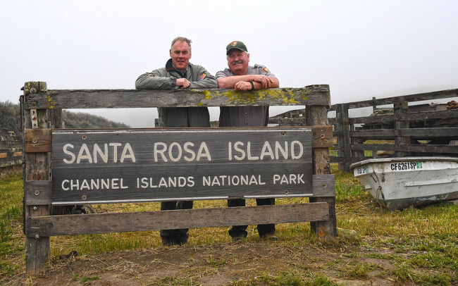 "Secretary Zinke and Park's staff stand behind a sign that reads, ""Santa Rosa Island Channel Islands National Park"""
