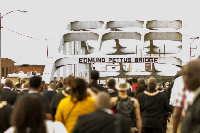 Photo of a large group of people walking across the historic Edmund Pettus Bridge in Selma, Alabama.