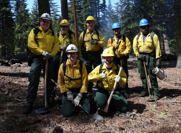 Secretary Zinke stands in the center of five men, two crouched below him, all men wear yellow uniforms and hardhats