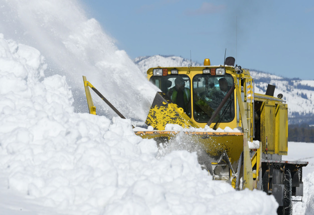Yellow snow plough moves large amounts of snow bank