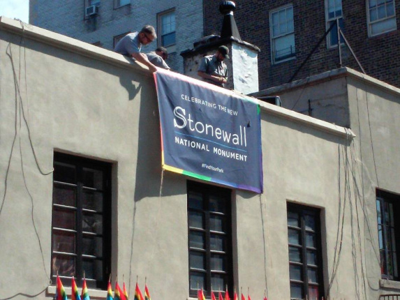 Three National Park Service employees roll down a navy blue banner commemorating the designation of the Stonewall National Monument.