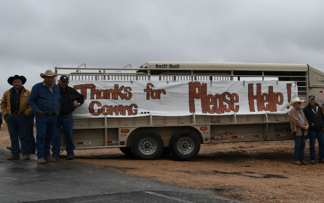"Two groups of men stand on either side of a large truck with a white banner on its side with writing painted on it in red ink saying, ""Thanks for Coming...Please Help!"""