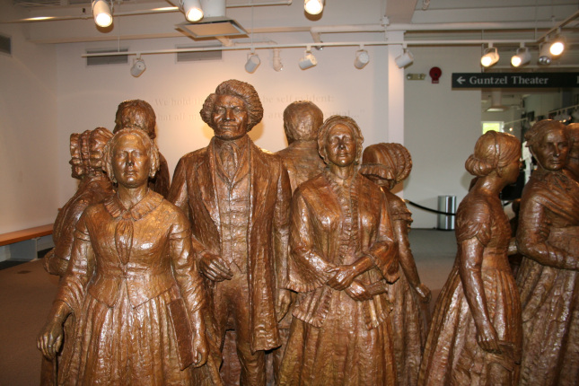 Approximately nine brown sculptured figures stand in a white, lighted room, facing different ways. A male figure stands between two female figures facing the camera, and all the figures are clothed in colonial style dress.