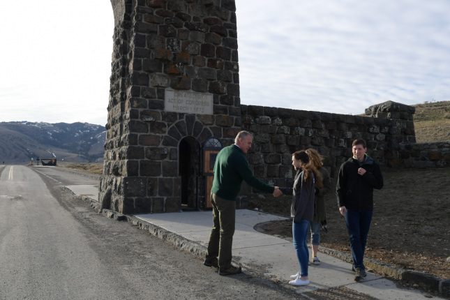 Secretary Zinke greets two visitors by side of road, below arch