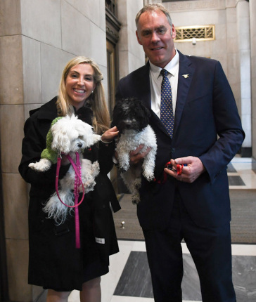 Secretary Zinke in vestibule, wearing a suit stands next to a woman, both holding dogs