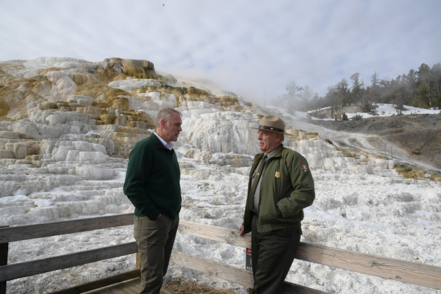 Secretary Zinke and a Parks' official stand near geothermic location in winter