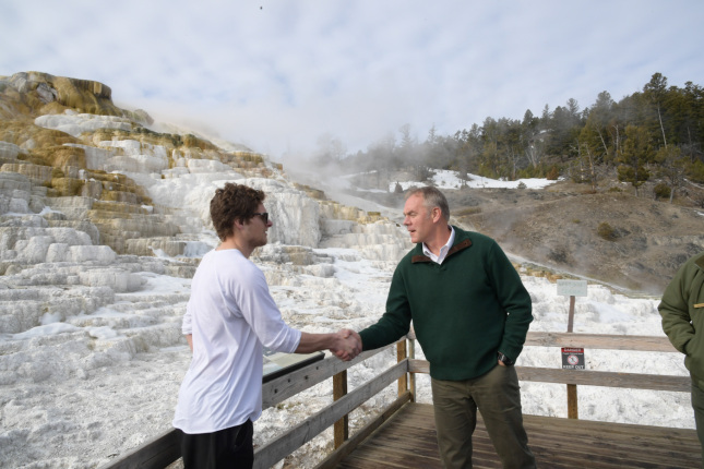 Secretary Zinke shakes hands with visitor in white shirt by geothermic locale in winter