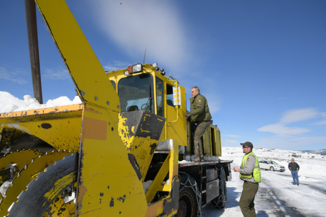 Secretary Zinke climbing aboard a yellow snow removal vehicle