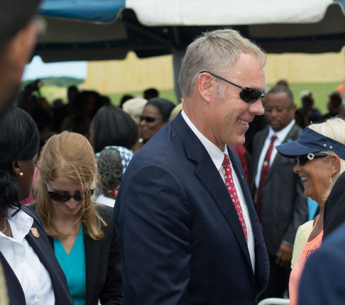 Secretary Zinke in profile, wearing sun glasses and a suit