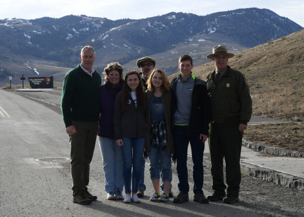 Secretary Zinke standing with family and Park employees by road