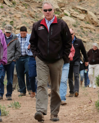 Secretary Zinke walks up a hill and in front of a group of men and women on a dirt road
