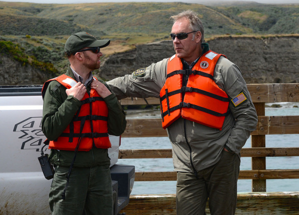 Secretary Zinke standing on a pier speaks to a man sitting on the bumper of a pickup truck; both wear orange life vests