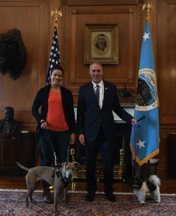 A tall woman stands with her mid-sized dog, next to Secretary Zinke eith his smaller dog