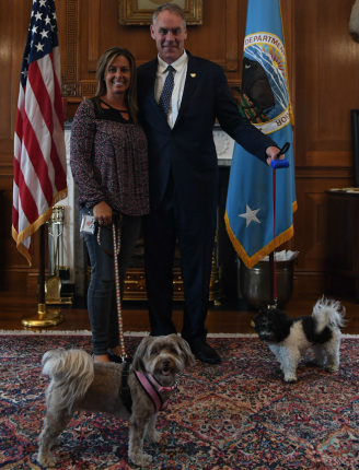 Secretary Zinke with his dog welcomes an Interior employee holding her dog on a colored leash and pink color
