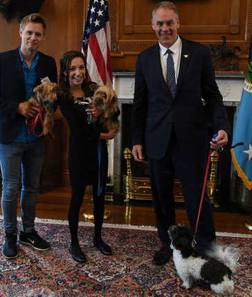 Secretary Zinke holding a dog on a leash, stands next to a man and woman each cradling a dog in their arms