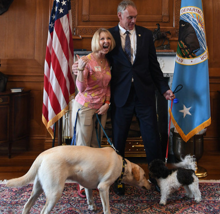 Secretary Zinke stands with a woman giving the thumbs up, both each have a dog on a leash