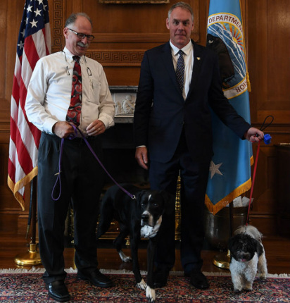 A man with a white shirt and necktie but no jacket, stands next to Secretary Zinke, also in a white shirt with a necktie, but wearing also a jacket, and both each have a dog on a leash