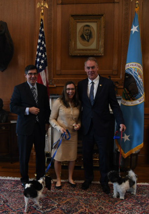 A man and woman, both with brown hair and dark glasses hold a small dog on a leash, joining Secretary Zinke and his dog on a leash