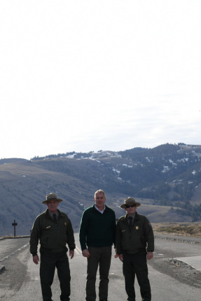 Secretary Zinke flanked by two Park employees, hills in background