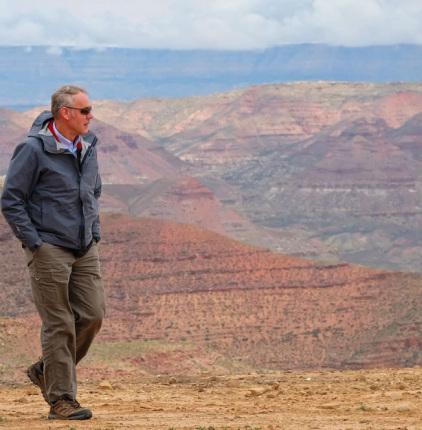 Secretary Zinke walks on rocky cliff overlooking ridges and hills on an arid landscape