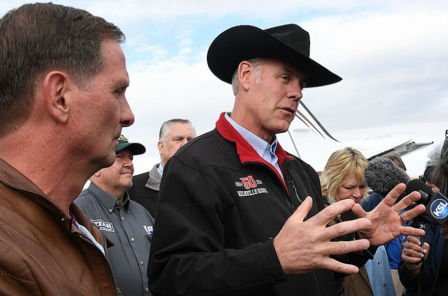 Secretary Zinke with black hat but no sunglasses speaks into a microphone as other persons look on