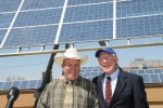 Secretary Ken Salazar and Milford High School teacher Andy Swapp stand in front of a newly installed solar panel at Milford High School in Utah.