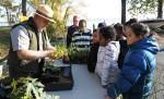 Children gather around a parks employee holding plants.