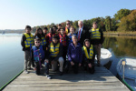 Secretary Jewell poses with a group of children in life vests on a dock with water and trees behind them