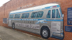 Photo of historic mural of a large Greyhound bus painted on a long brick wall.