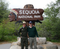 Secretary Zinke stands next to a man under an official sign for Sequoia National PArk