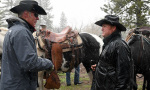 Secretary Zinke speaks to a man in a black raincoat as the rain falls on them and horses nearby