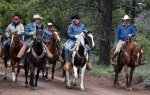 Secretary Zinke rides on horseback with four other person on horseback beside him on a dirt trail