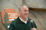Secretary Zinke smiling in-front of a National Park Service sign