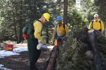 Secretary Zinke starts a controlled burn while two men watch; all three wear hardhats and yellow uniforms