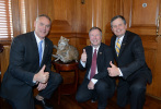 Secretary Zinke and two men also in suits crouch and give thumbs up next to cat miniature