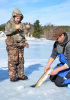 A boy stands on a frozen lake while a man kneels down and pulls a large fish out of a hole in the ice.