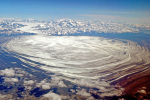 An aerial photo taken from high in the sky shows a huge, flat glacier of ice spreading out from a mountain range.