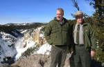 Secretary Zinke stands on a snowy peak next to a Park official wearing a hat