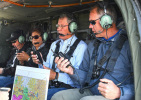 Secretary Zinke sits strapped into a helicopter along with two men and a woman all with walky-talkies