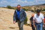 Secretary Zinke walks along a ridge with a group of men under a blue sky