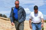 Secretary Zinke wears blue next to a man in white as they walk along under a blue sky