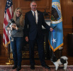Secretary Zinke holds his small dog by the leash, standing next to a woman who holds a dog in her arms