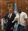 Secretary Zinke holds his dog in his right arm standing next to an Interior employee also holding his dog in his right arm