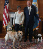 Secretary Zinke stands next to a woman in a white shirt with a furry, light-colored dog