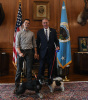 Secretary Zinke holds a dog meeting another dog held on a leash by another man