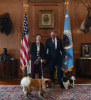 Secretary Zinke in a dark jacket stands next to a woman in a dark jacket, both with different dogs