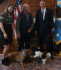 Secretary Zinke stands, holding dog on a leash that plays with a dog lying down, with on older man and younger woman next to Secretary Zinke