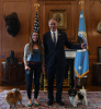 Secretary Zinke holds his dog still using a leash, while standing beside him a young woman does likewise