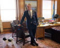 Secretary Zinke in his office leans against a leather chair, holding a leash with a dog