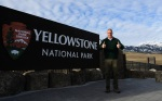 Secretary Zinke stands by a sign for a Yellowstone National PArk